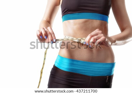 Athletic slim woman measuring her waist by measure tape after a diet. isolated on white background. High resolution  - stock photo