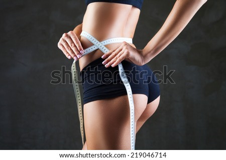 Athletic slim woman measuring her waist by measure tape after a diet over dark gray background - stock photo