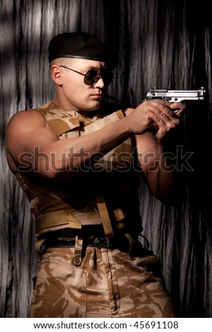Athletic soldier in camouflage aiming with handgun - stock photo