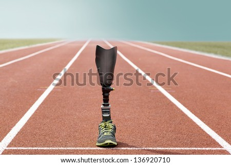 Athletic sports prosthesis of a disabled athlete stands on a tartan track