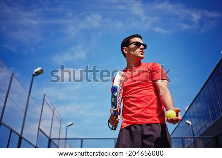 Athletic sportsman ready to feed ball in paddle game on beautiful blue sky background, paddle game outside, healthy lifestyle concept - stock photo