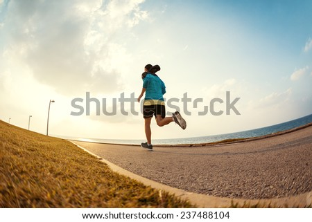 athletic sportsman running in the park near the ocean in the sunset