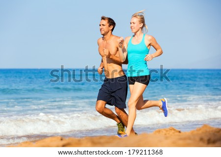 Athletic sporty couple jogging together on the beach