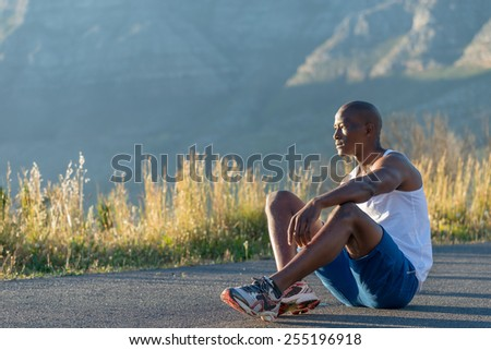 Athletic, sporty, muscular, healthy black male sitting after losing a race along a road outdoors with a mountain background