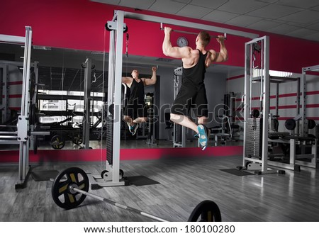 Athletic strong bodybuilder execute exercise in sport gym hall - stock photo