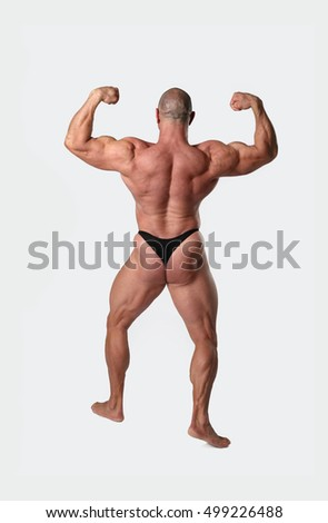 Athletic strong man poses and showing strained muscles of his naked body on gray background