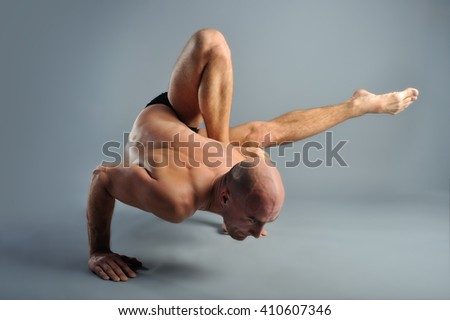 Athletic Strong Man Practicing Difficult Yoga Pose On A Studio Gray Background