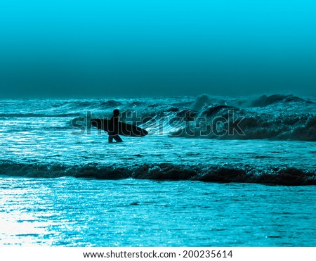 Athletic surfer with board on a wave in the ocean - stock photo