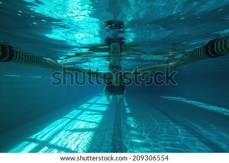 Athletic swimmer swimming towards camera in the swimming pool at the leisure centre - stock photo