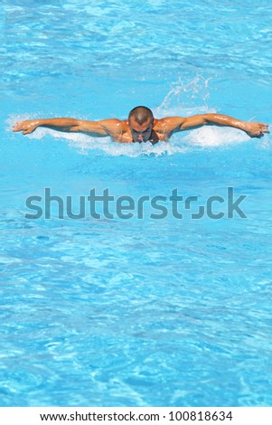 Athletic swimmer training hard in a swimming pool - stock photo