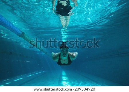 Athletic swimmer training on her own in the swimming pool at the leisure centre - stock photo
