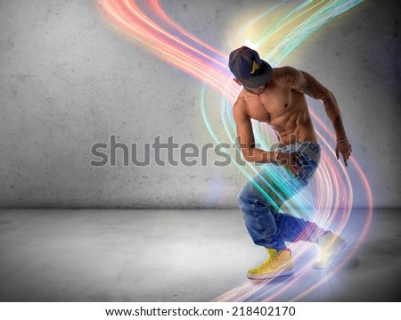 Athletic trendy shirtless young man in a hat doing a break dance routine surrounded by colorful light streaks - stock photo