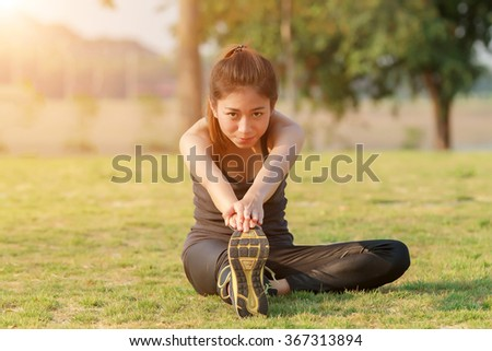 Athletic woman asia warming up and Young female athlete sitting on an exercising and stretching in a park before Runner outdoors, healthy lifestyle concept. - stock photo