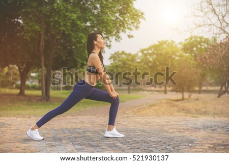 Athletic woman asian warming up and Young female athlete sitting on an exercising and stretching in a park before Runner outdoors, healthy lifestyle concept