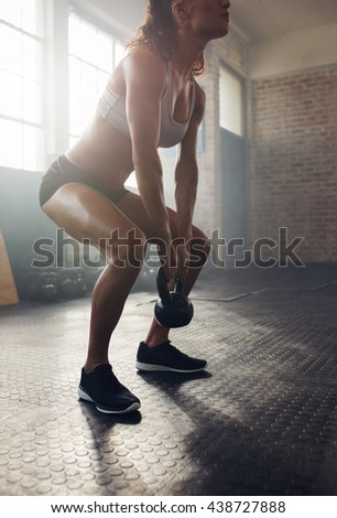Athletic woman exercising with kettle bell while being in squat position. Muscular woman doing crossfit workout at gym. - stock photo
