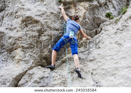 Athletic woman free climbing on a high rock wall  - stock photo
