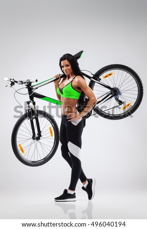 Athletic woman holding bicycle on her shoulder on gray background