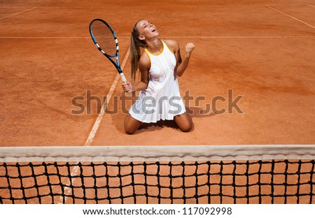 Athletic woman in a white tennis suit enjoys victory sitting on her knees on the court - stock photo