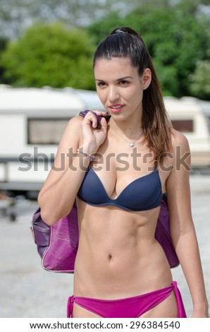 Athletic woman in caravan parking. She is wearing two pieces swimwear and holding her bag at the shoulder, her abs looks perfect. Many caravans as background. Vertical picture - stock photo