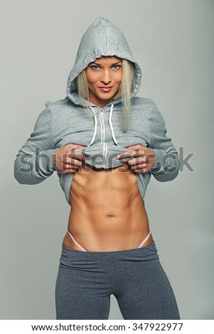 Athletic woman in grey hoodie showing her muscular stomach.