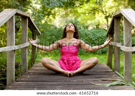 athletic woman in pink dress practicing yoga on wooden bridge in park