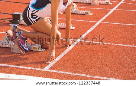 Athletic woman in start position, to run. - stock photo