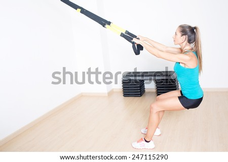 Athletic woman makes TRX exercise - stock photo