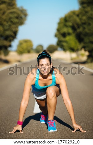 Athletic woman on running sprint challenge in countryside road. Fitness female runner in ready start line pose outdoors. - stock photo