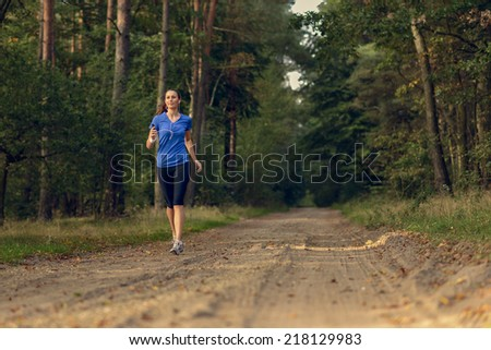 Athletic woman out jogging in a forest approaching the camera along a dirt track through the trees in a health and fitness concept