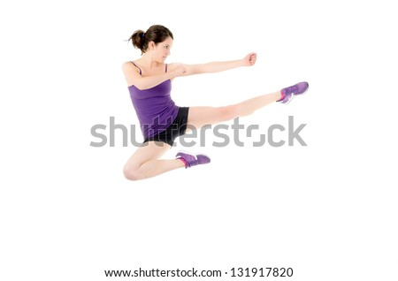 Athletic woman performing a flying side kick isolated on a white background