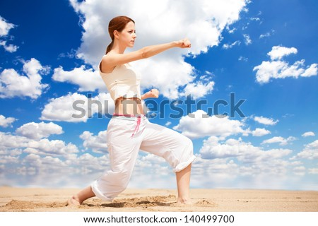 athletic woman performing a kick in an sand beach - stock photo