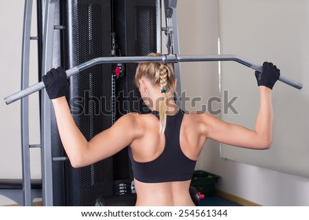 Athletic woman performing back exercise in gym - stock photo
