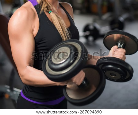 athletic woman pumping up muscles with dumbbells. - stock photo
