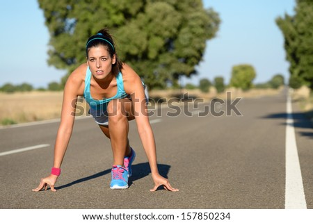 Athletic woman running in countryside road. Fitness female runner in ready start line pose outdoors in summer sprint challenge. - stock photo
