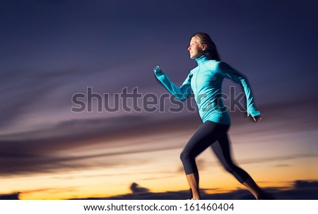 Athletic woman running jogging outside, training outdoors. Running at sunset dusk with motion blur - stock photo