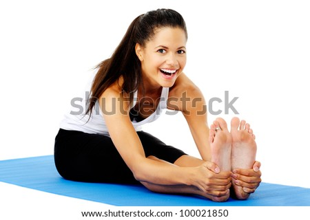 Athletic woman smiling while she stretches forward, Part of a collection of yoga poses by a fit active mixed race woman; sit-up pose. - stock photo