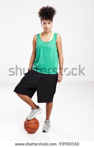 Athletic woman standing with a basketball under her foot. Studio shot.