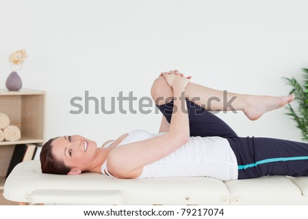 Athletic woman stretching her leg while looking at the camera - stock photo