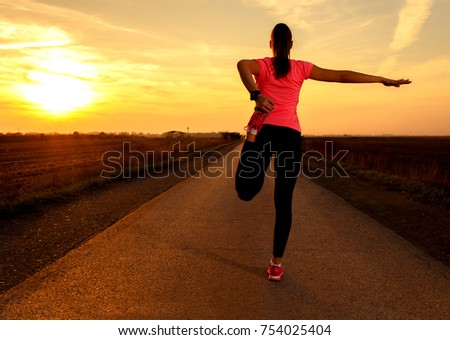 Athletic woman stretching her muscles on rural road during sunset.