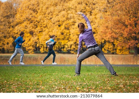 Athletic woman stretching in autumn glade after jogging - stock photo