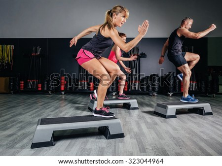 Athletic woman trainer doing aerobic class with steppers to people group on a fitness center. Sport and health concept. - stock photo