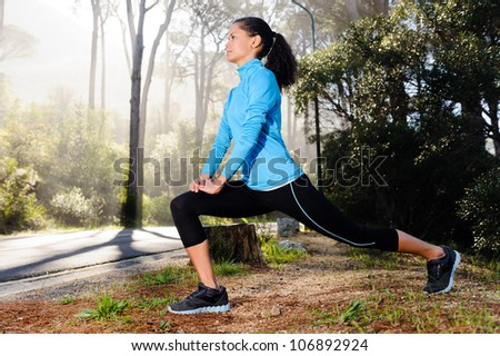 Athletic woman warming up before her morning workout in the forest mountain road. Runner training outdoors, healthy lifestyle concept. - stock photo