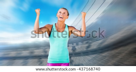 Athletic woman with arms up against view of a stadium - stock photo