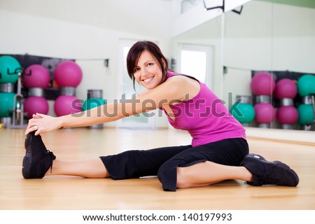 Athletic woman working out in a gym sitting on the hardwood floor stretching her muscles and warming up before commencing her workout
