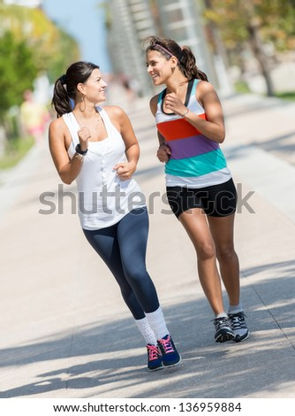 Athletic women running outdoors looking very happy - stock photo