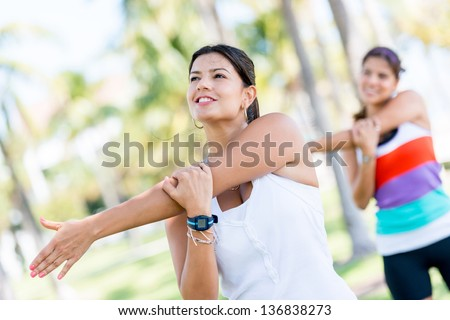 Athletic women stretching her arms at the park