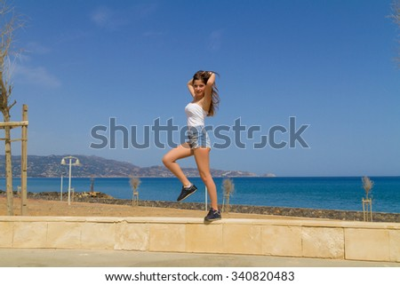 Athletic young beautiful expressive and joyful dark haired teenage girl in jean shorts, enjoys the sun while workingout at a park by the ocean.