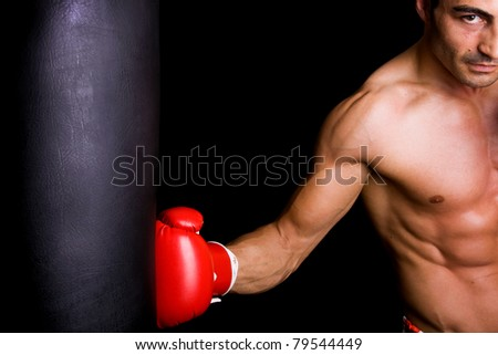 Athletic young boxer fighter punching bag over black background