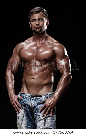 athletic young caucasian man in studio on black background