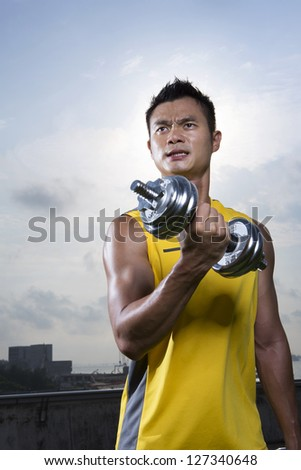 Athletic Young Chinese man exercising outdoors with dumbbells. Muscular Asian man exercising with weight training equipment. Male fitness concept.